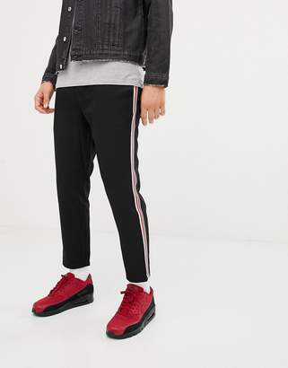 Pull&Bear pants in black with red and white side stripe
