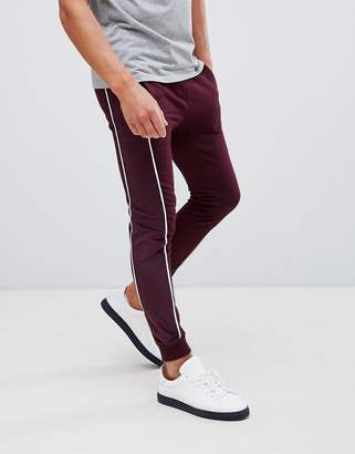 Asos DESIGN super skinny sweatpants with velour side stripe and piping in burgundy
