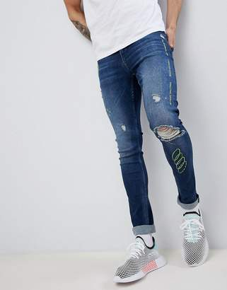 Asos DESIGN extreme super skinny jeans in dark wash blue with rips and embroidery