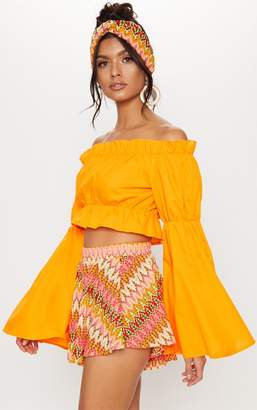 ecbe65e5a67d38 PrettyLittleThing Orange Ruched Bardot Flare Sleeve Crop Top