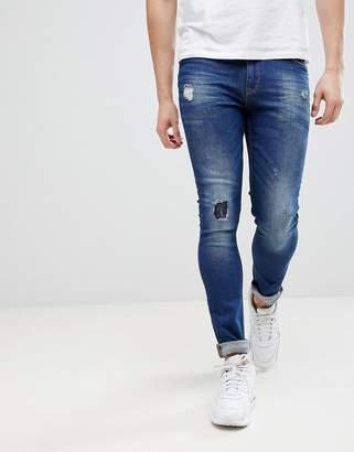 Asos Design Super Skinny Jeans In Dark Wash Blue With Abrasions