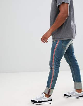 Asos DESIGN super skinny jeans in mid wash with rips and side stripe