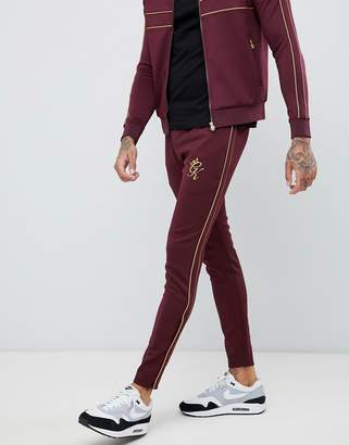 Gym King skinny joggers in burgundy with gold side stripes