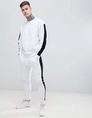 Asos DESIGN tracksuit oversized sweatshirt/skinny joggers with side stripe in white marl and black