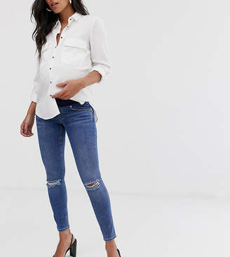 162aaf8422c1d Asos DESIGN Maternity lisbon mid rise skinny jeans in mid wash blue with  frayed knee rips