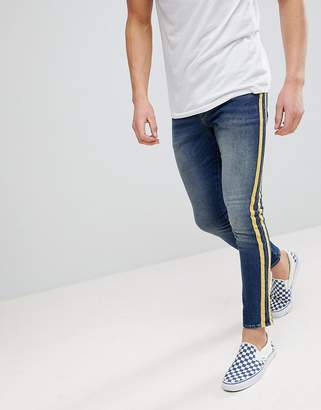 Asos DESIGN super skinny jeans in mid wash with yellow side stripes