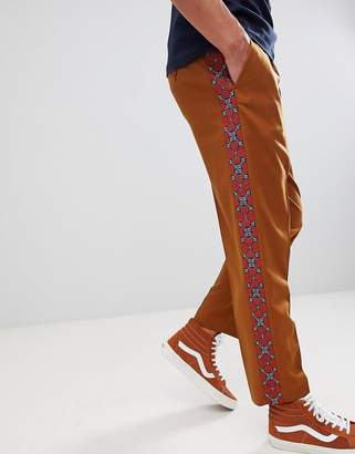 Asos DESIGN tapered smart pants in tan with geo-tribal embroidered side stripe