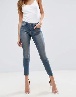 Asos DESIGN LISBON Skinny Mid Rise Jeans in Dita Tinted Mid Wash with Reverse Stepped Hem