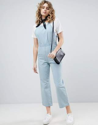 Asos Design DESIGN denim cross back jumpsuit in midwash blue