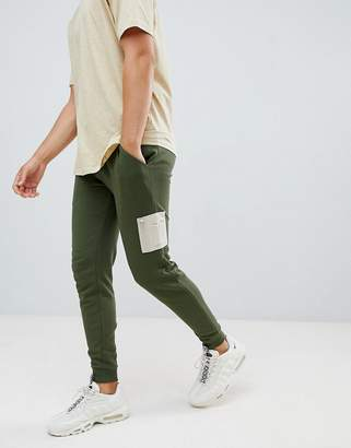Asos DESIGN skinny joggers with contrast MA1 pocket in green
