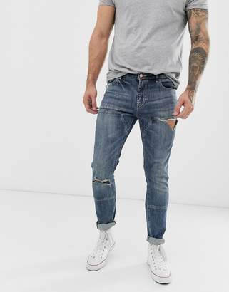 Asos Design DESIGN skinny jeans with cut and sew panels and rips in dark wash blue