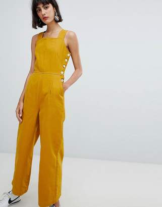 Asos Design DESIGN denim jumpsuit with side buttons in mustard