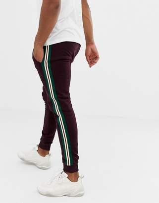 Asos DESIGN skinny sweatpants with side stripe taping in burgundy