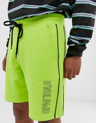 ASOS DESIGN jersey shorts in washed neon with text print