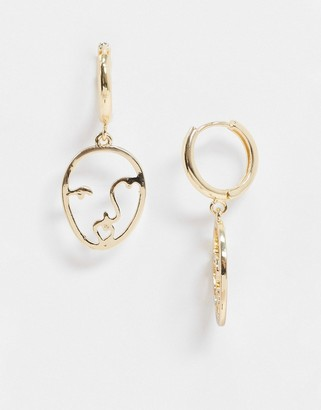ASOS DESIGN hoop earrings with abstract face charm in gold tone