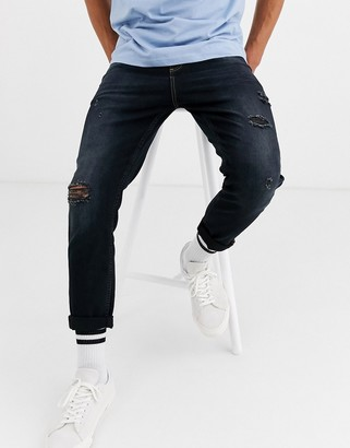 ASOS DESIGN tapered carrot fit jeans in washed black with abrasions