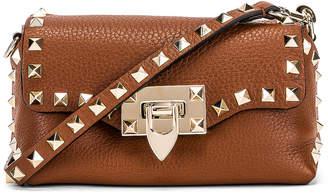 Valentino Rockstud Mini Crossbody Bag in Bright Cognac | FWRD