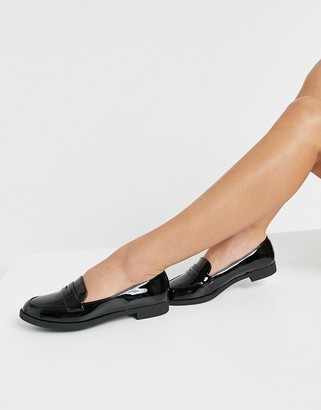 Accessorize flat loafers in black patent