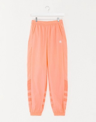 adidas large trefoil track pant in coral