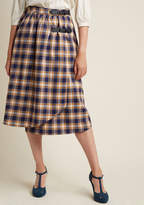 AP327B Time the debut of this wrap skirt right and you'll win the heart of everyone in the quad! Heralding a highland-inspired design with buckled black straps, side pockets, and an indigo, marigold, and ivory plaid pattern, this Alice's Pig separate is an intel