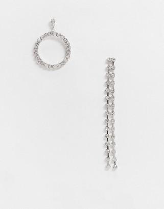 True Decadence asymmetric drop earrings in silver rhinestone