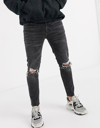 Asos Design DESIGN cropped skinny jeans in washed black with raw hem and knee rips