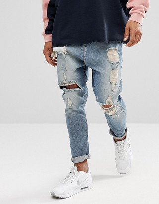 Asos Design DESIGN drop crotch jeans in vintage light wash blue with heavy rips