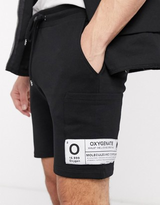 Asos DESIGN jersey skinny shorts in black with side pockets and patch