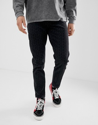 ASOS DESIGN tapered jeans with all over print in black