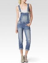 gwen stefani  Who made  Gwen Stefanis white print tee, blue denim overalls, and wedge sneakers?