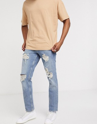 ASOS DESIGN stretch slim jeans in mid wash blue with heavy rips