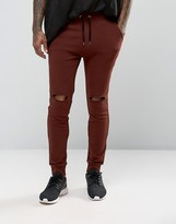 Asos Super Skinny Joggers With Knee Rips In Dark Red
