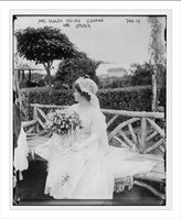 Library Images Newswire Photo (L): Mrs. Waldo Irving Shuman, nee Speyer, seated on bench, holding bouquet of flowers