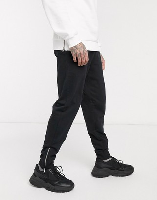ASOS DESIGN organic tapered sweatpants in black with silver zip cuffs