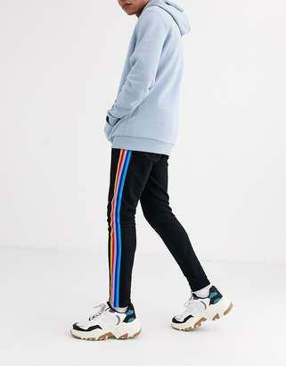 Asos Design DESIGN skinny joggers with rainbow side tape & fixed hem in black