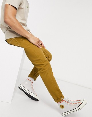 Asos DESIGN slim jeans in mustard