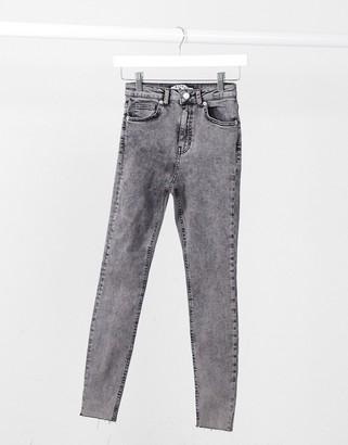 NA-KD high waisted raw hem skinny jeans in black