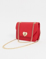 Asos Design DESIGN cross body bag with heart twist lock in red