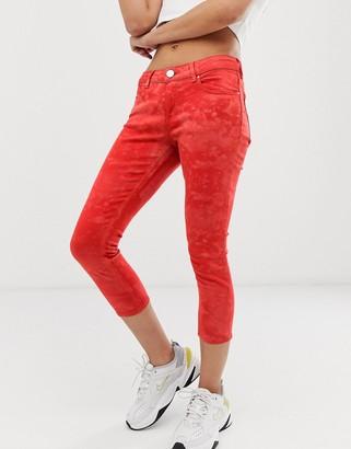 Asos DESIGN Whitby low rise skinny jeans in orange tie dye