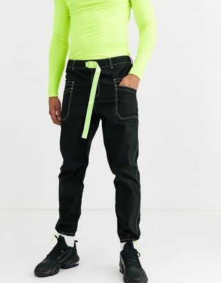 ASOS DESIGN tapered cargo pants in black with neon contrast stitch and webbed belt