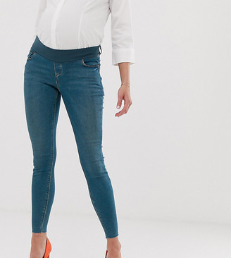 Asos DESIGN Maternity Ridley high waisted skinny jeans in aged wash blue with raw hem with under the bump waistband