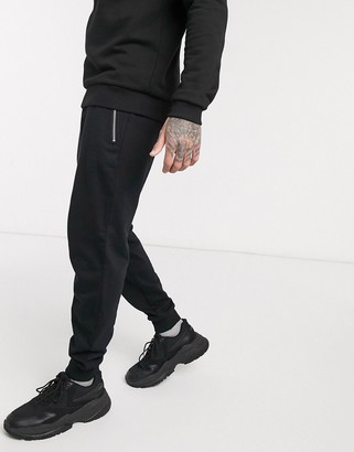 ASOS DESIGN organic tapered sweatpants in black with silver zip pockets