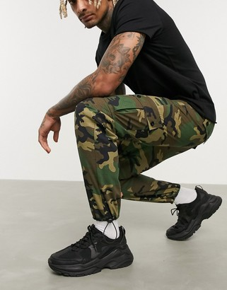 Asos DESIGN tapered cargo trousers with toggles in camo print