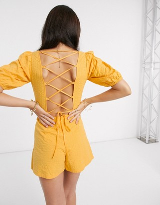 ASOS DESIGN seersucker lace up back playsuit in yellow
