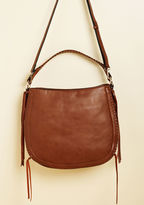 13145 How many compliments can you collect while carrying this brown hobo purse? Sling this faux-leather bag's topstitched shoulder strap over your arm and find out! Frilled up with side tassels and a crossbody option, this cool carryall is destined to shine on