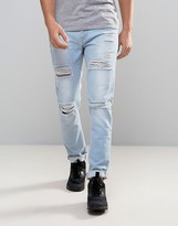 Asos Skinny Jeans With Heavy Rips In Bleach Wash Blue