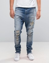 Asos Drop Crotch Stacked Jeans With Rips And Bleaching In Mid Blue
