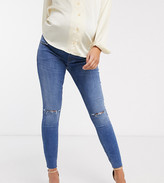 Asos DESIGN Maternity Ridley high waisted skinny jeans in mid wash blue with rips with over the bump band