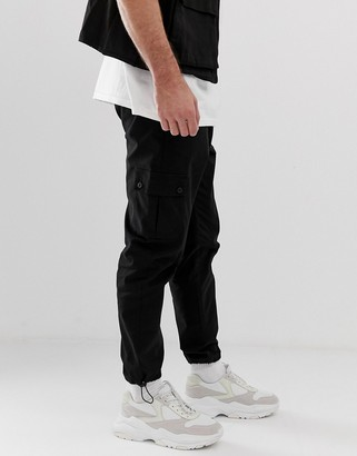 ASOS DESIGN tapered cargo pants in black with toggles