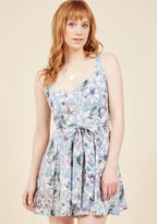 Upon donning this pale blue romper by Collectif for a day outdoors, you wonder just how to accessorize such a pretty piece. Reviewing the sash-tied waist, skirt-like legs, pockets, and muted floral print of your ensemble, you decide a genuine smile, a ski